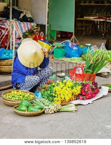 Asian Trader Selling Fresh Flowers And Vegetables In Street Market