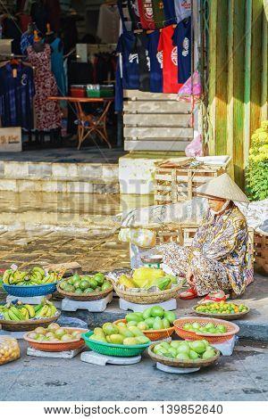 Asian Trader Selling Fresh Bananas Mangoes And Lime