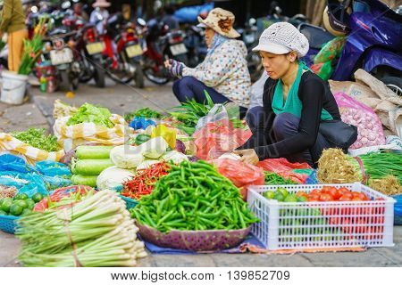Asian Trader Selling Mixed Fresh Vegetables In The Street Market