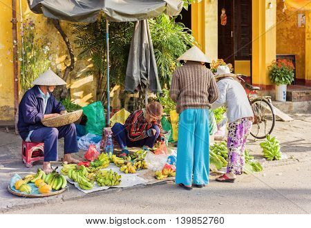Asian Traders Selling Bunches Of Bananas