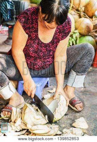 Asian Woman Cutting And Selling Fresh Coconut In The Market