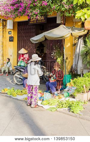 Asian Woman Selling Bunches Of Bananas