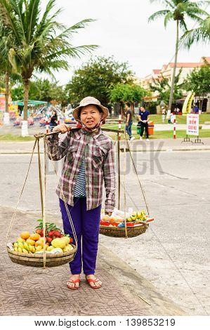 Asian Woman Trader Carrying Rambutan Mango Banana And Mandarin