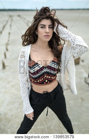Cute girl stands on the sand outdoors. She wears black pants, multi-colored top with patterns and a white cardigan. Her left hand is on the hair, right arm hangs along the body. She looks into the camera with parted lips. She has rings on the right hand.