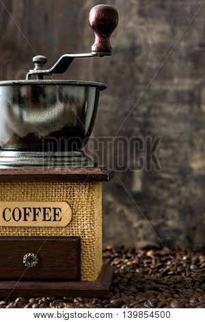 Coffee grinder and coffee beans on rustic wooden background