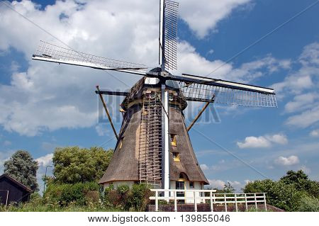 Dutch Windmill in the Polder under a blue Sky with white Clouds