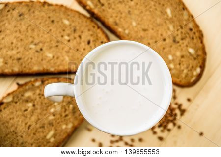 white Cup of yogurt on a background of fresh corn bread on a wooden table
