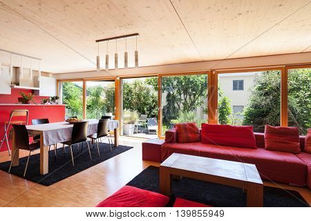 Living room of an eco house, red divan and kitchen