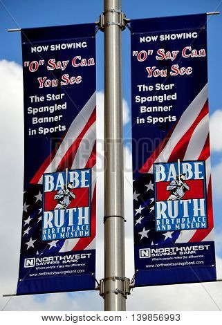 Baltimore Maryland - July 23 2013: Banners promoting an exhibition at the Babe Ruth Birthplace and Museum hung on a street light yardarm on Pratt Street