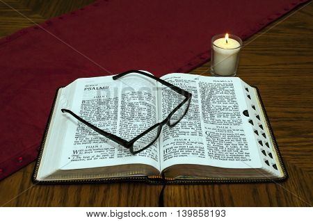 Open Bible On Wood Table With Lighted Candle