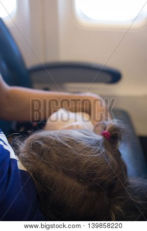 Baby sleeps on his mother's lap during the flight by plane. Selective focus on the child's head.