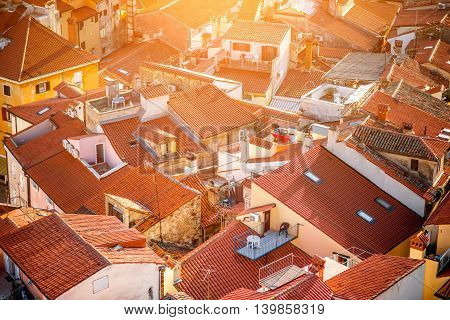 Top view on the old buildings with red roofs in Piran town at the sunset in Slovenia