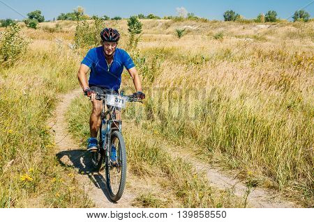 Gomel, Belarus - August 9, 2015: Mountain Bike cyclist riding track in meadow at sunny day, healthy lifestyle active athlete doing sport.