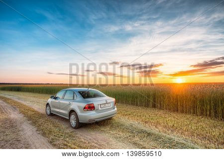 Gomel, Belarus - June 13, 2016: Volkswagen Polo Car Parking On Wheat Field. Sunset Sunrise Dramatic Sky On A Background In Sunny Evening.