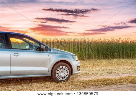 Car Parking On Wheat Field. Sunset Sunrise Dramatic Sky On A Background In Sunny Evening. Drive And Freedom Concept