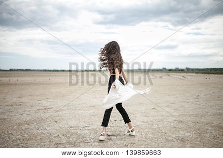 Girl with windy hair stands on the sand on the cloudy sky background. She wears black pants, multi-colored top with patterns and a white cardigan. Her hands with the cardigan are behind her back. Photographed from the back. Outdoors. Horizontal.