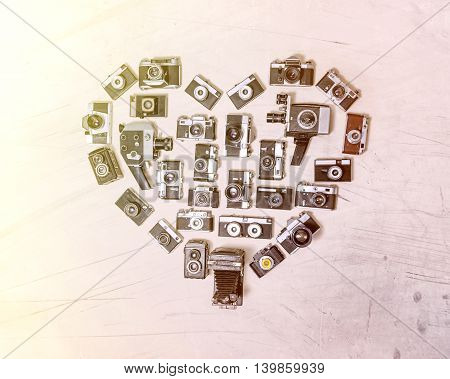 Unusual image of heart assembled from retro cameras on a light pink background with texture