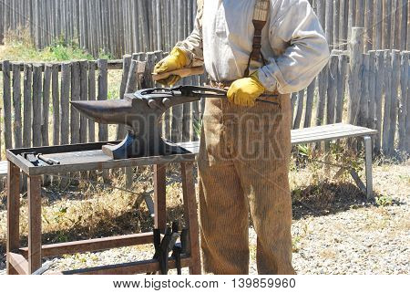 Male blacksmith working on a horse shoe outdoors.