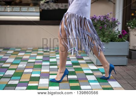 Girl in the lilac jacket and blue shoes walks on the multi-colored tiles in the city street. Close-up photo. Outdoors. Horizontal.