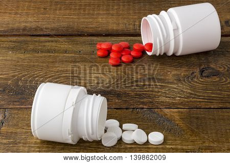 Various medical pill bottles on a wooden background