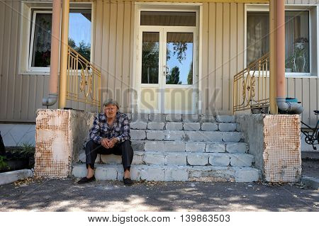 Lyman, Ukraine, 13.07.2016. Old man sitting on stairs in front of the nursery home.