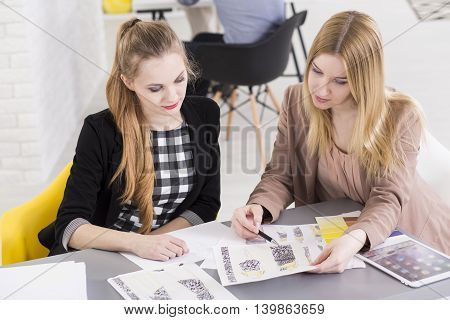 Two women comparing the design projects with the pickers on the desk