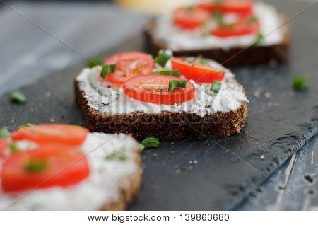 Bruschetta with feta cheese, fresh tomatoes and spices on a black rustic table