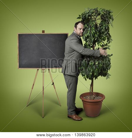 Businessman hugging a tree at office - studio shot