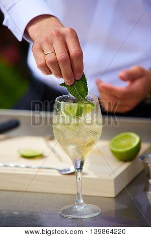 Bartender in nature preparing alcoholic drink mojito