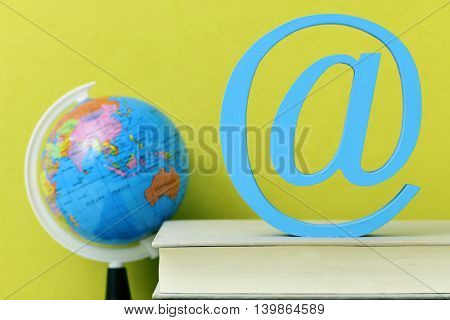 a three-dimensional blue at sign on a pile of books and a globe, depicting the concepts of the e-learning, the e-teaching, the distance education or the educational technology
