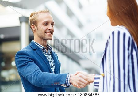Young businessman shaking hand to partner outdoor