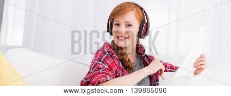 Happy ginger woman with headphones holding pencil and sheet of paper panorama