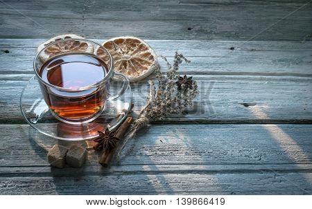 Transparent cup of black tea and dry twig herb dried oranges cinnamon sticks sugar and anise star on wooden background with copy space. Toned