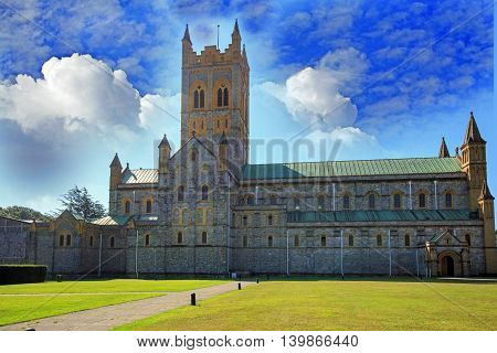A large Abbey in the Devon Countryside with a vivid blue cloudy sky