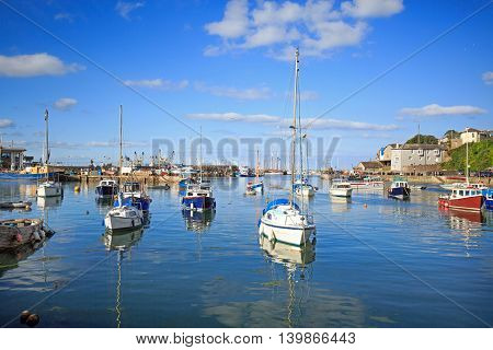 Seascape in Brixham Harbour with a bright blue sky and calm sea