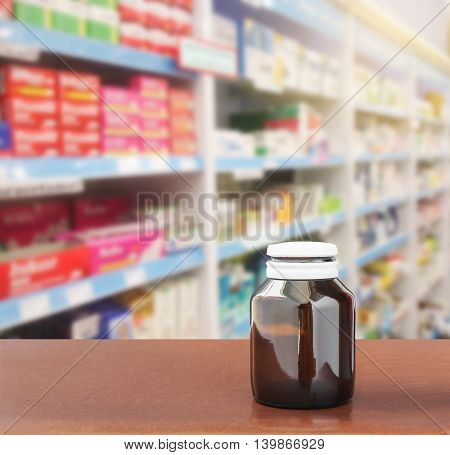 Medicine bottle on table top on blurred pharmacy store