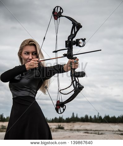 Young woman with a compound bow over clouds