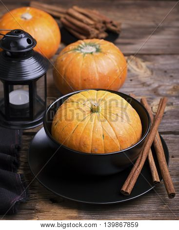 Autumn themed tableware. Black pottery, long cinnamon sticks, small ripe pumpkin on a simple wooden background. selective focus