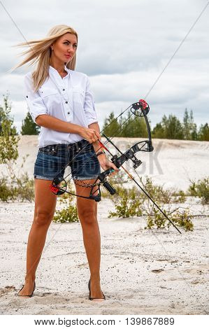 Young woman with a compound bow in desert
