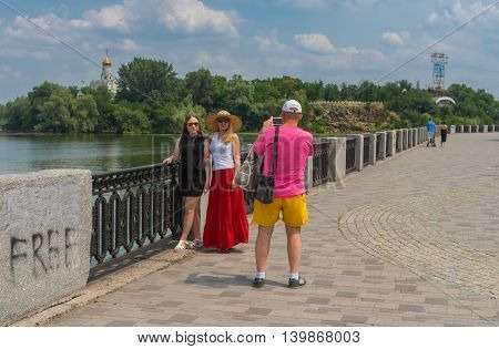 DNEPROPETROVSK UKRAINE - JULY 10, 2016: People doing family portrait while walking on the Dnepr river embankment at weekend in Dnepropetrovsk, Ukraine at  July 10, 2016