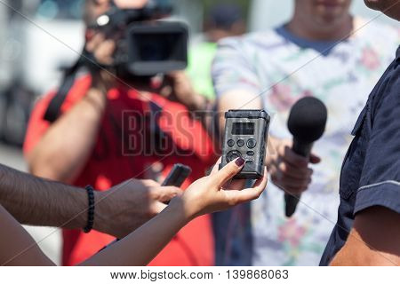 TV interview. Journalists holding microphone and voice recorder conducting TV or radio interview.