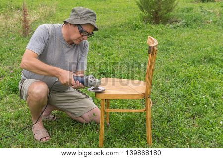 Mature man doing restoration of old chair using angle grinder