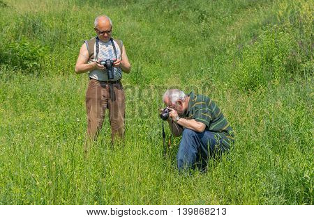 Dnepropetrovsk Ukraine - May 28 2014: Two mature amateur photographers shoots wild nature in a local park