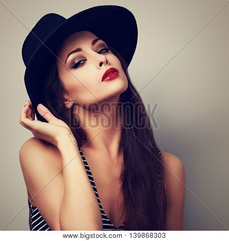 Hot sexy female woman with bright makeup and red lipstick in black hat posing. Toned vintage portrait