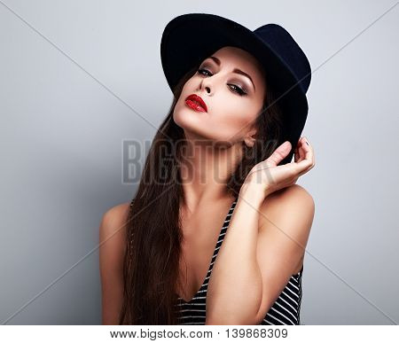 Hot sexy female woman with bright makeup and red lipstick in black hat posing on blue background