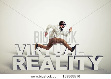 Young bearded man in virtual reality glasses running between 3d words isolated over white background