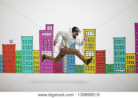 Young bearded man in virtual reality headset is photographed in mid-air jump isolated over white background with colorful buildings drawn on it