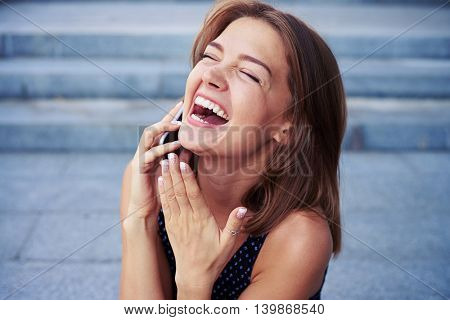 Attractive cheerful female is speaking on the phone and laughing sincerely over grey street stairs background
