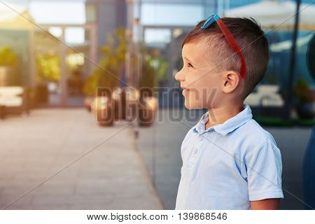 Side view of small boy with sunglasses on his head who is standing near mirror window of modern building and looking up at the sky