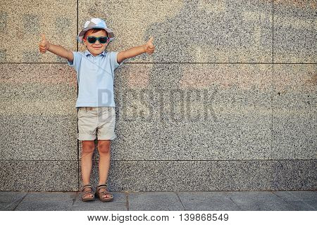 Small boy in casual summer clothes and sunglasses is standing near the wall in the street and giving thumbs up